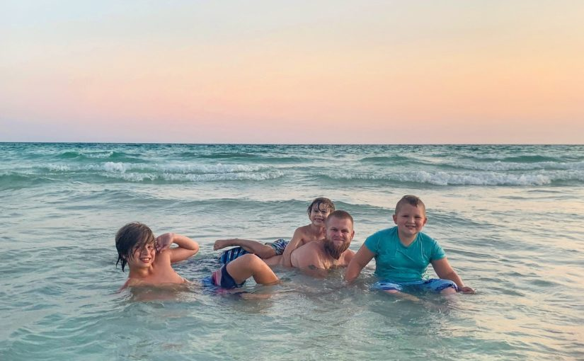 Guest photo showing family sitting in the ocean enjoying the waves