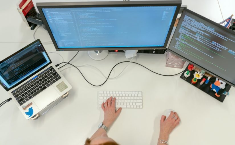 Female software engineer codes at her desk with computers
